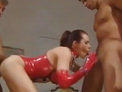 Horny misstress in red latex uses 3 slaves for her pleasure