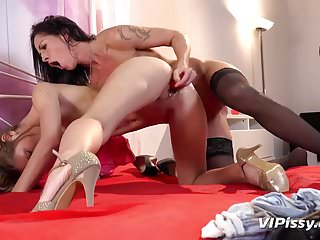 Naughty girls share a strap-on and their golden piss