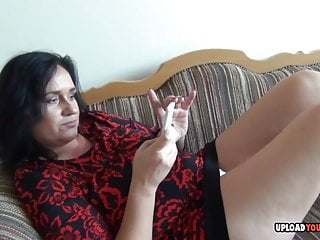 Mature licks a condom and fingers herself...